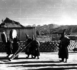 photo of monks in Tibetan monastery blowing liturgical horns
