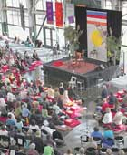 Large Shambhala event in public hall, with banners, speaker's platform and many attendees