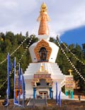 a photo of The Great Stupa of Dharmakaya, the gilt parts of the monument shining in the sun along with many prayer flags