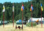 A photo of five flagstaffs in the front of Magyal Pomera encampment grounds where Sun Camp at Shambhala Mountain is heald