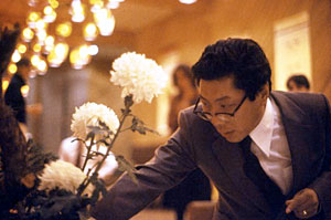 photo of Chogyam Trungpa doing Flower Arranging in a formal hall