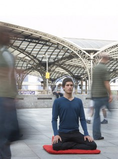 Man meditating in train station