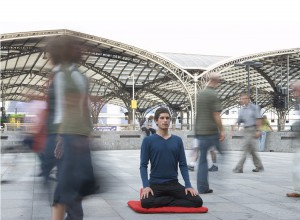 Man meditating in train station