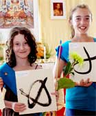 A picture of two young ladies of Shambhala showing their finished calligraphies in the shrine room